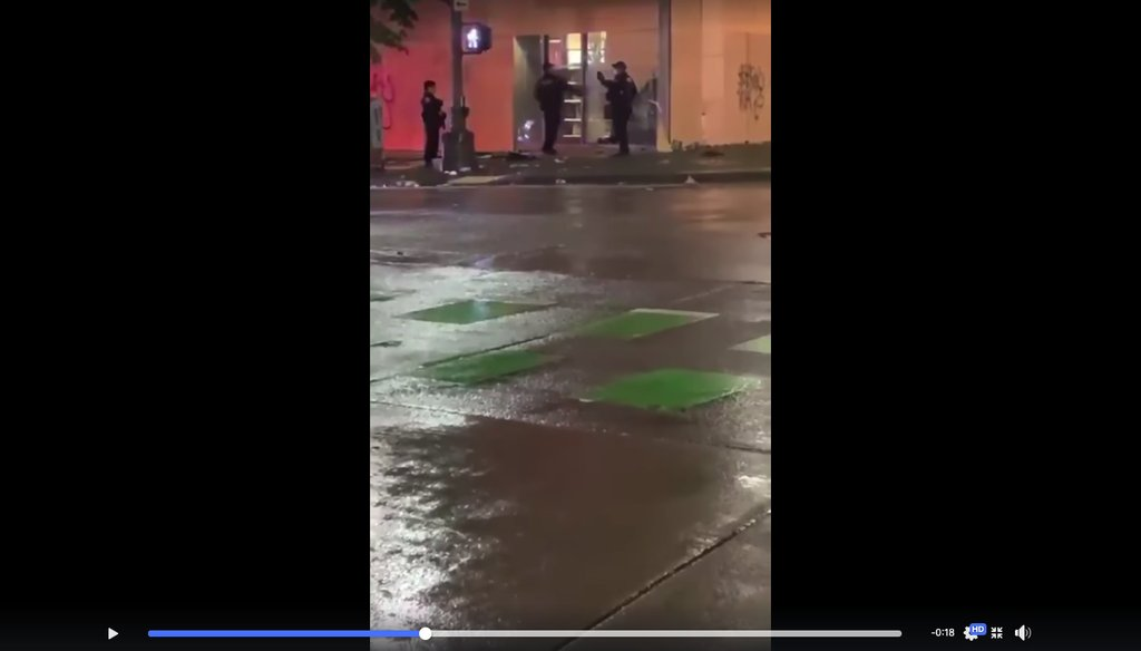 This is a screenshot from a video showing a Seattle police officer trying to gain entry to a building.