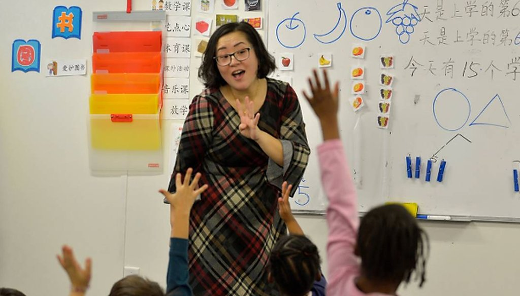Teacher Yan Han helps students as she teaches a kindergarten class at East Voyager Academy in Charlotte.