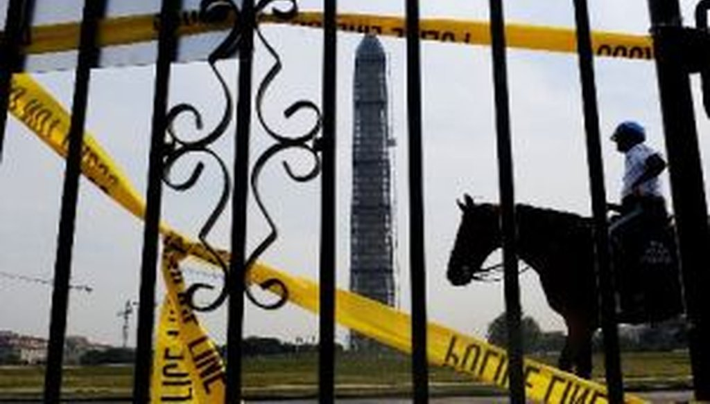 A mounted police officer passes in front of the Washington Monument and the World War II memorial on the Mall in Washington during a federal shutdown on Oct. 3, 2013.