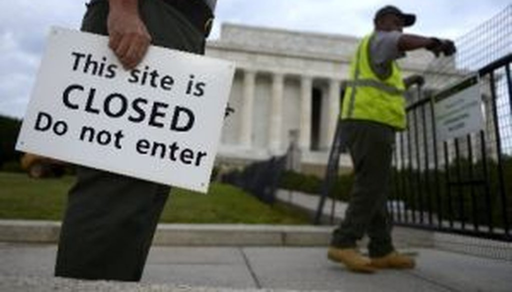 U.S. Park Service personnel erect barriers and hang signs as they close the Lincoln Memorial in Washington, on Oct. 1, 2013, the start of a federal government shutdown.