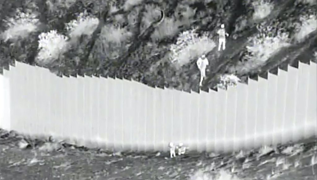 A photo taken from night video provided by the U.S. Customs and Border Protection shows smugglers after they dropped two children from the top of border barrier in Santa Teresa, N.M., on March 30, 2021. (AP)