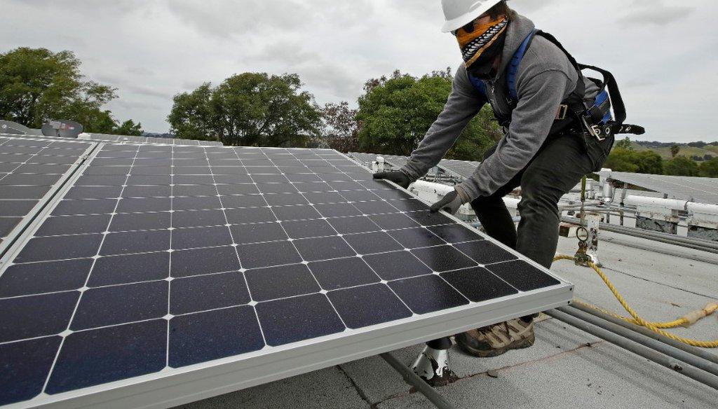 Gen Nashimoto, of Luminalt, installs solar panels in Hayward, Calif., in April 2020. (AP Photo/Ben Margot)