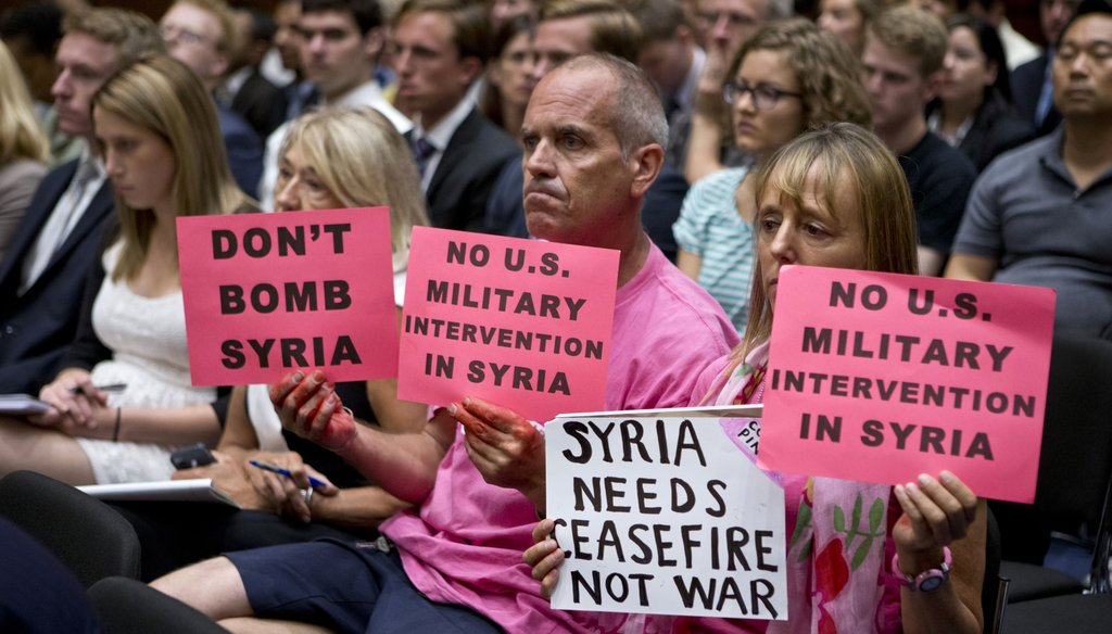 Protestors hold signs during a Sept. 3, 2013 hearing on Capitol Hill against U.S. military intervention in Syria. Photo credit: Associated Press.