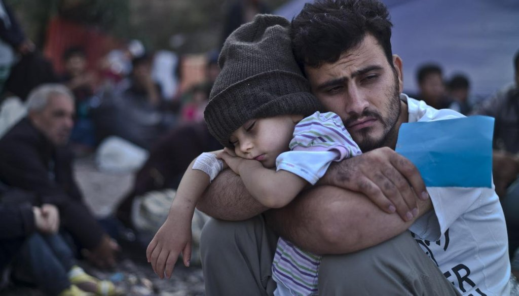 A Syrian refugee child sleeps in his father's arms while waiting at a resting point to board a bus in October 2015, after arriving on a dinghy from the Turkish coast to the northeastern Greek island of Lesbos. (AP photo)