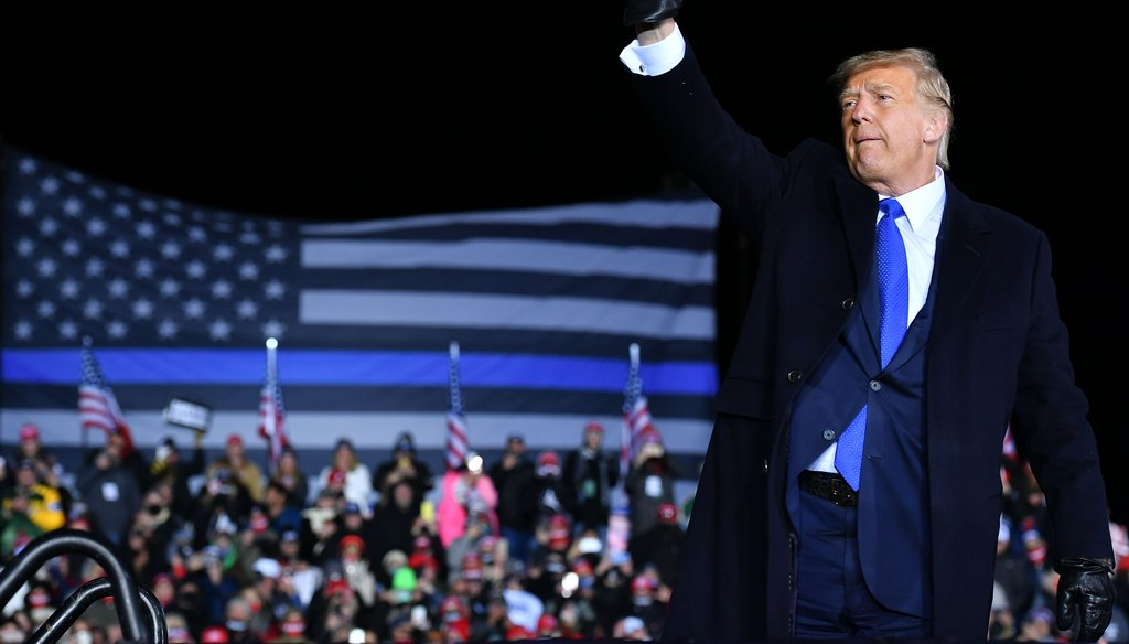 President Donald Trump waves as he leaves a campaign rally at Waukesha County Airport in Waukesha, Wisconsin on October 24, 2020. A large Thin Blue Line flag is visible behind the president.(Getty Images).