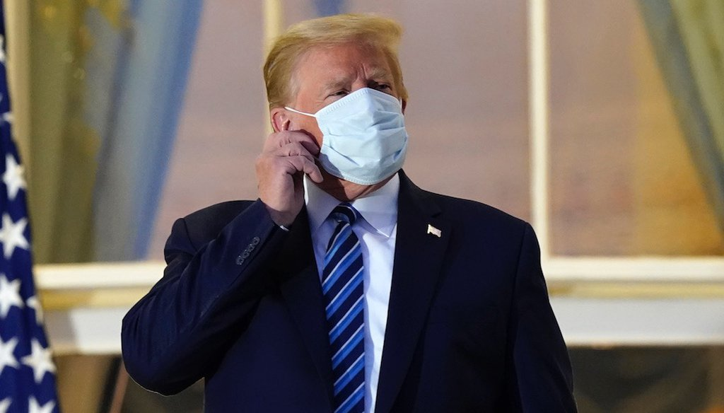 President Donald Trump removes his mask on his return to the White House  after leaving Walter Reed National Military Medical Center, in Bethesda, Md.  (AP Photo/Alex Brandon)