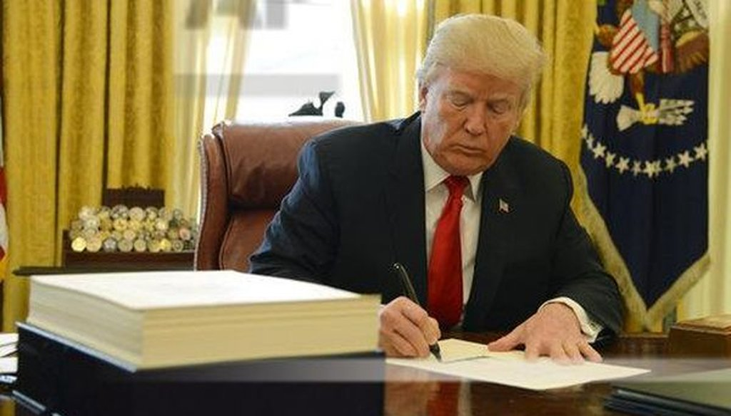 President Donald Trump signs a tax bill, stacked on his desk, in the Oval Office on Dec. 22, 2017. (Mike Theiler/Pool via CNP)