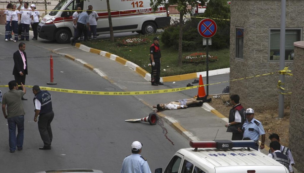 An unidentified man lies on the ground lifeless after an attack outside of the U.S. Consulate in Istanbul, Turkey, Wednesday, July 9, 2008. (AP)