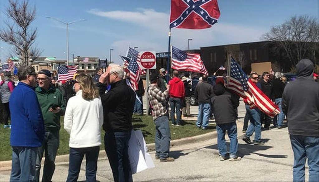 One man attending an April 18, 2020, rally in Brookfield, Wis., to protest coronavirus stay-at-home orders carried a Don't Tread on Me flag and a Confederate flag. (Milwaukee Journal Sentinel)