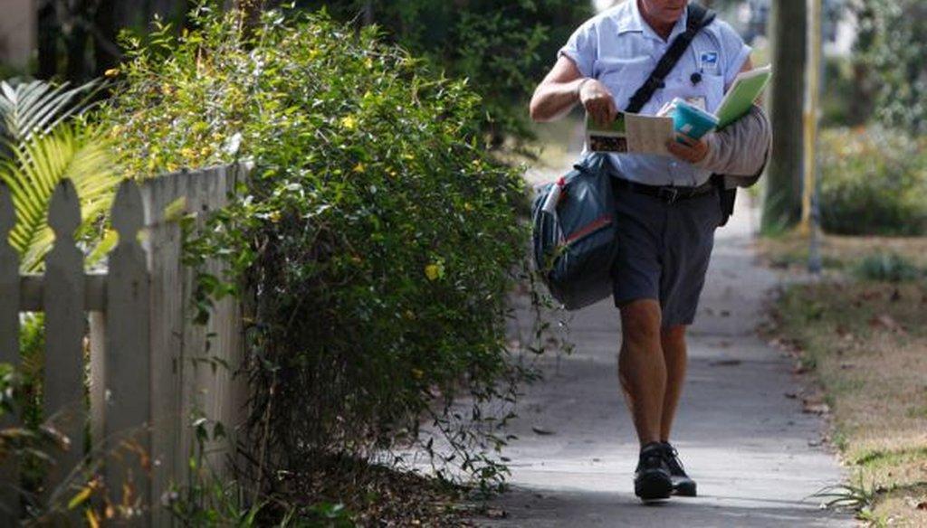 Mail carrier Derek Wilkins makes deliveries on Burlington Ave. N. in St. Petersburg, Fla. (Lara Cerri/Tampa Bay Times)