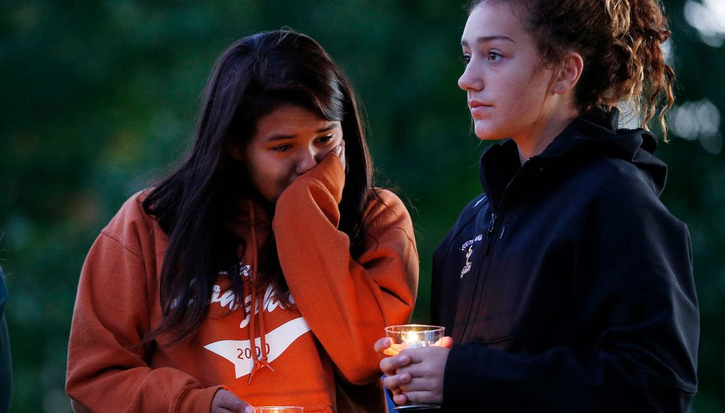People hold candles during a prayer vigil Oct. 3, 2015, in Winston, Ore. The vigil was held in honor of the victims of the fatal shooting at Umpqua Community College. (AP)