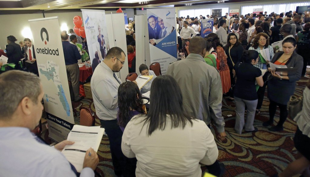 Job seekers check out companies at a job fair in Miami Lakes, Fl. on Aug. 14, 2013. Photo credit: AP.