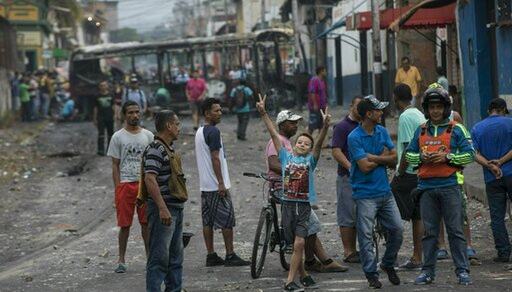 Residents gather in the streets where a public bus was burned during clashes between Bolivarian National Guards and anti-government protesters in Urena, Venezuela, near the border with Colombia, Sunday, Feb. 24, 2019. (AP)