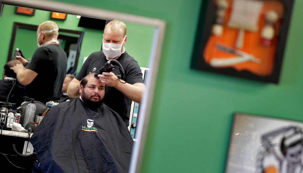 Jeff Guebara gets his hair cut by Roman Naumenko at Uptown Barbershop Friday, May 8, 2020, in Phoenix. Hair salons and barbershops across Arizona began reopening Friday after being closed for more than a month by order of the governor (AP Photo/Matt York)