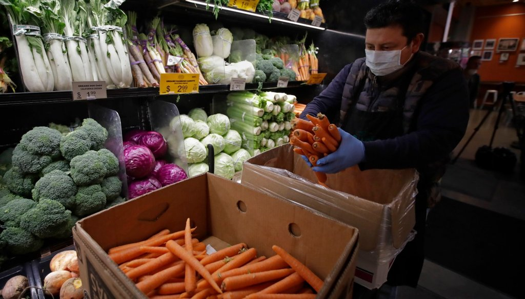 In this March 27, 2020, file photo, a worker, wearing a protective mask against the coronavirus, stocks produce before the opening of Gus's Community Market in San Francisco. (AP Photo/Ben Margot, File)