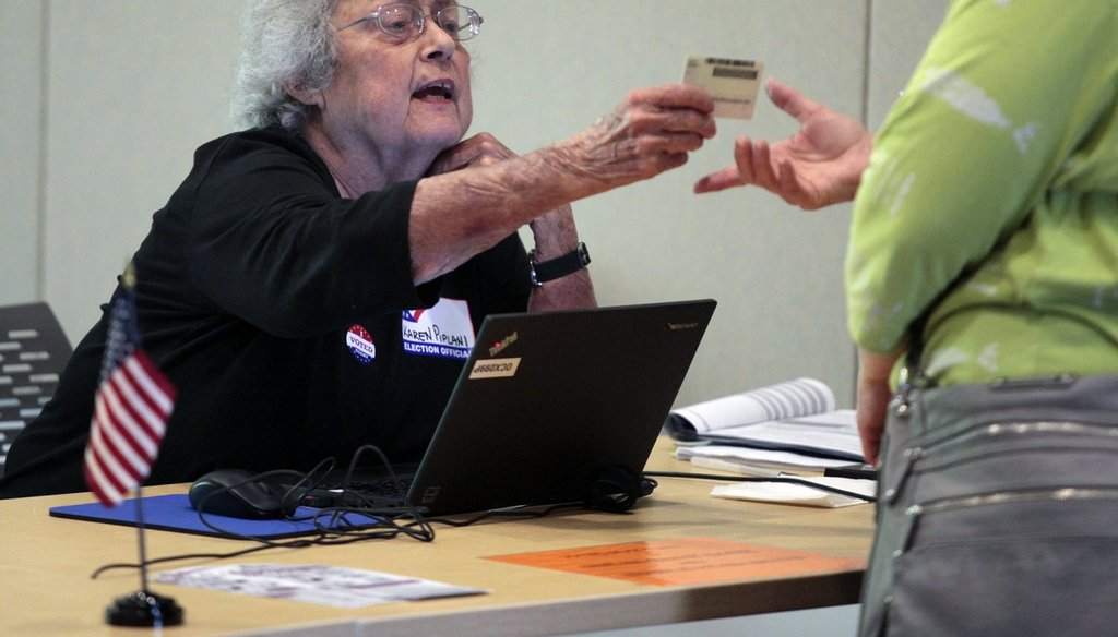 A precinct official in Chapel Hill, NC checks a photo ID in 2016.