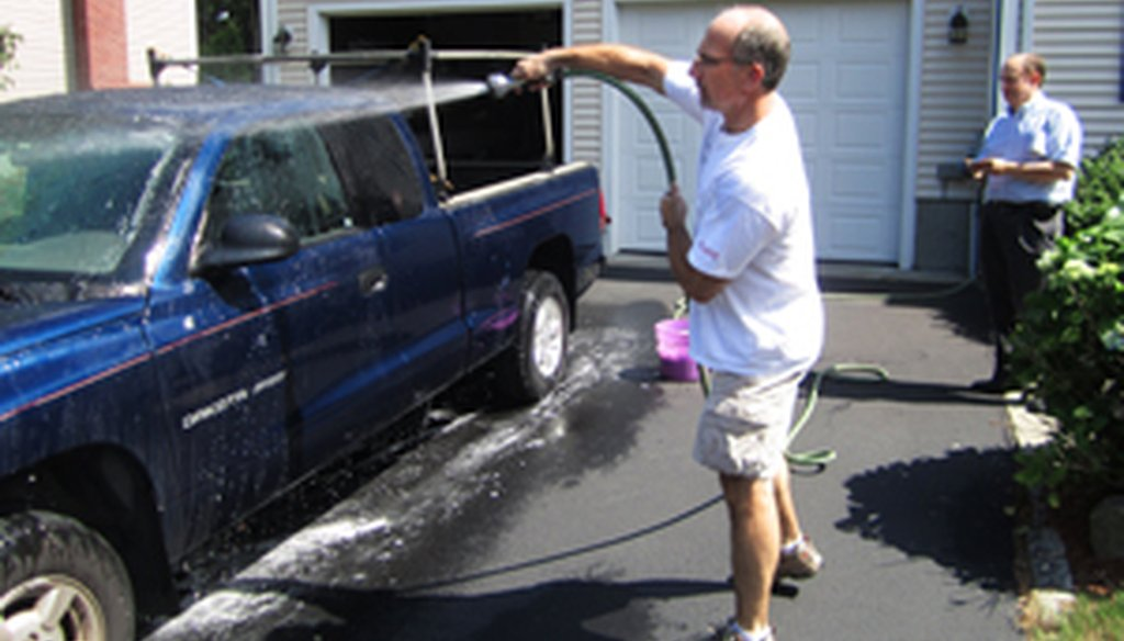 PolitiFact car wash experts Tom Mooney (with the hose) and Gene Emery (watching the time) do their experiment.