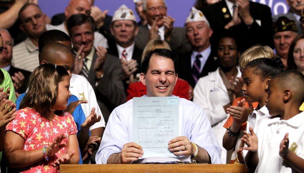 Gov. Scott Walker winks at the crowd after signing the 2013-'15 state budget.