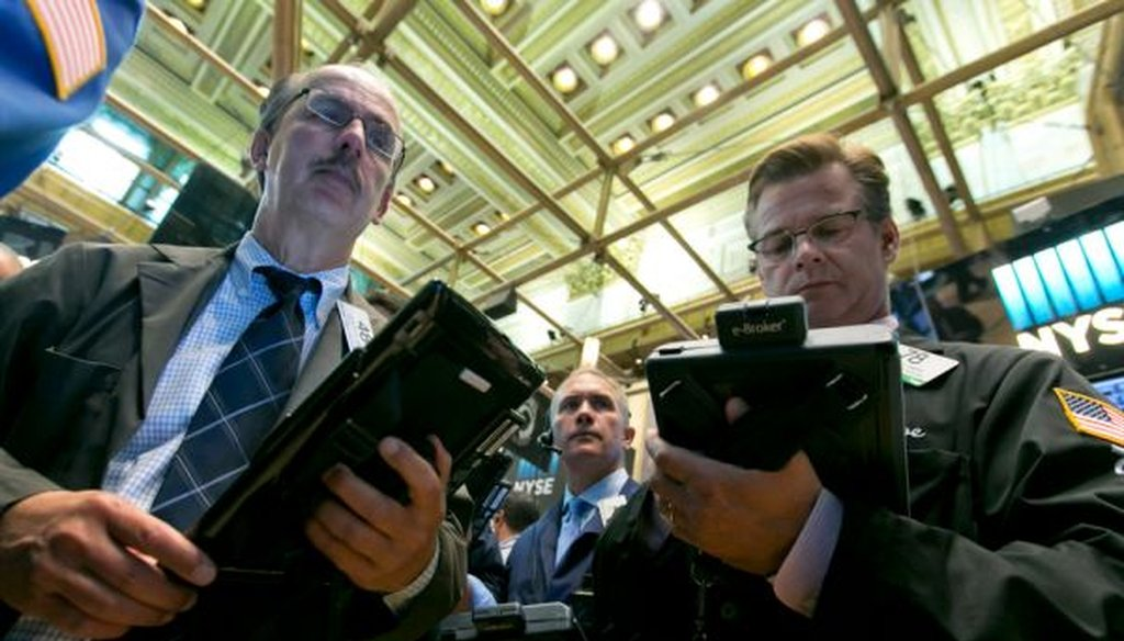 Traders Joseph Dente, Timothy Nick and Steven Capo work on the floor of the New York Stock Exchange on Aug. 4, 2015. (AP/Richard Drew)