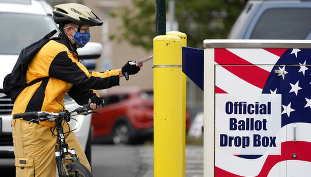 Cyclist Mickey McDiarmid votes by dropping her completed ballot into a ballot drop box Monday, Oct. 19, 2020, in Bellingham, Wash. (AP)
