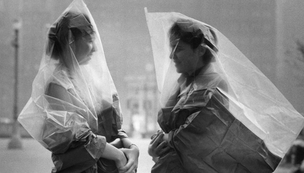 War surplus gas capes are used by Meriel Bush, left, and Ruth Neuer, in an attempt to dodge the eye-stinging effects of a low-hanging smog and smoke in Philadelphia in 1953. Some social media posts incorrectly said this was taken in 1918. (AP)