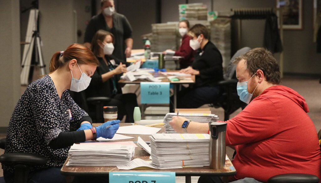 Poll workers check absentee ballot envelopes for signature on Nov. 3, 2020, at the Milwaukee Central Count facility. (Michael Sears/Milwaukee Journal Sentinel)
