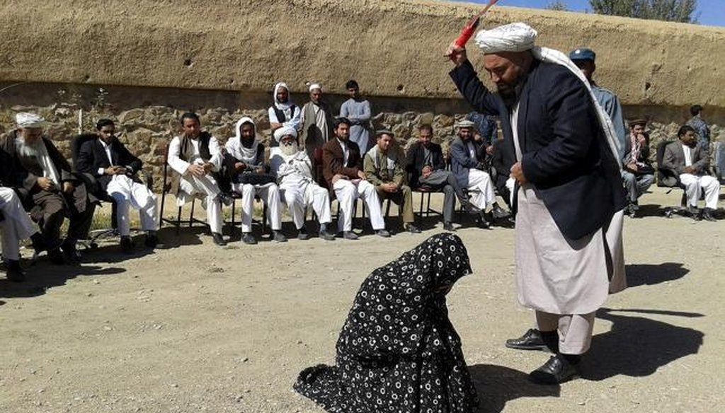 A fake news story about girls slated for execution in Saudia Arabia appears to be the same image as an Afghan judge hitting a woman with a whip in front of a crowd in Ghor province, Afghanistan, on Aug. 31, 2015.  (Reuthers/Pajhwok News Agency)