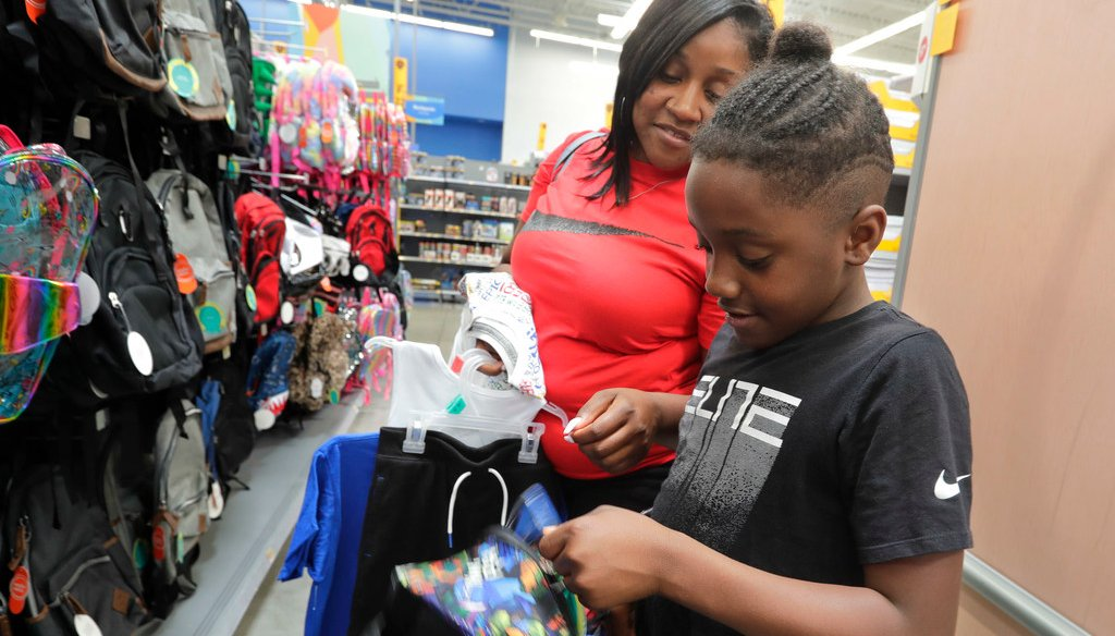 Carolyn Harris helps Nyzer Pendleton, 10, buy a backpack for school Friday at the Super Walmart in Greendale. He chose a backpack for when he starts school in Milwaukee in the fall. (Photo: Rick Wood / Milwaukee Journal Sentinel