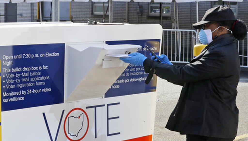 Marcia McCoy drops her ballot into a box outside the Cuyahoga County Board of Elections, Tuesday, April 28, 2020, in Cleveland, Ohio. (AP)