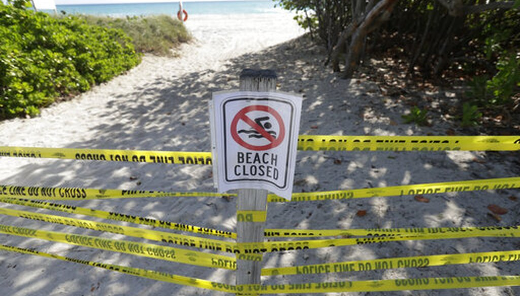 """A beach entrance is cordoned off, Saturday, March 21, 2020, in Surfside, Fla. Miami-Dade County's mayor ordered all beaches, parks and """"non-essential"""" commercial and retail businesses closed Thursday because of the new coronavirus pandemic. (AP)"""