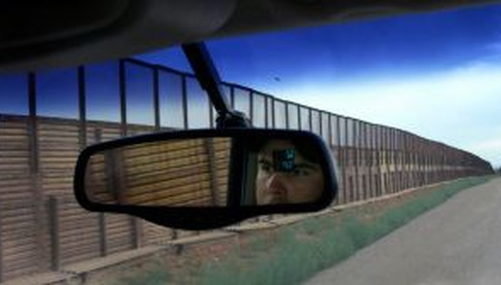 A border patrol agent drives along the border fence in Naco, Arizona. (2010)