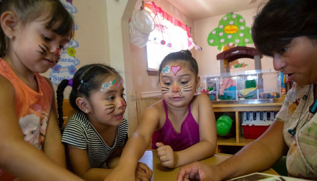 Maria Moreno reads to Mia Lopez (4), Ariana S‡nchez (3) and Leyla Lopez (6) at her daycare, Happy Faces Child Care in Milwaukee, in July 2019. File photo