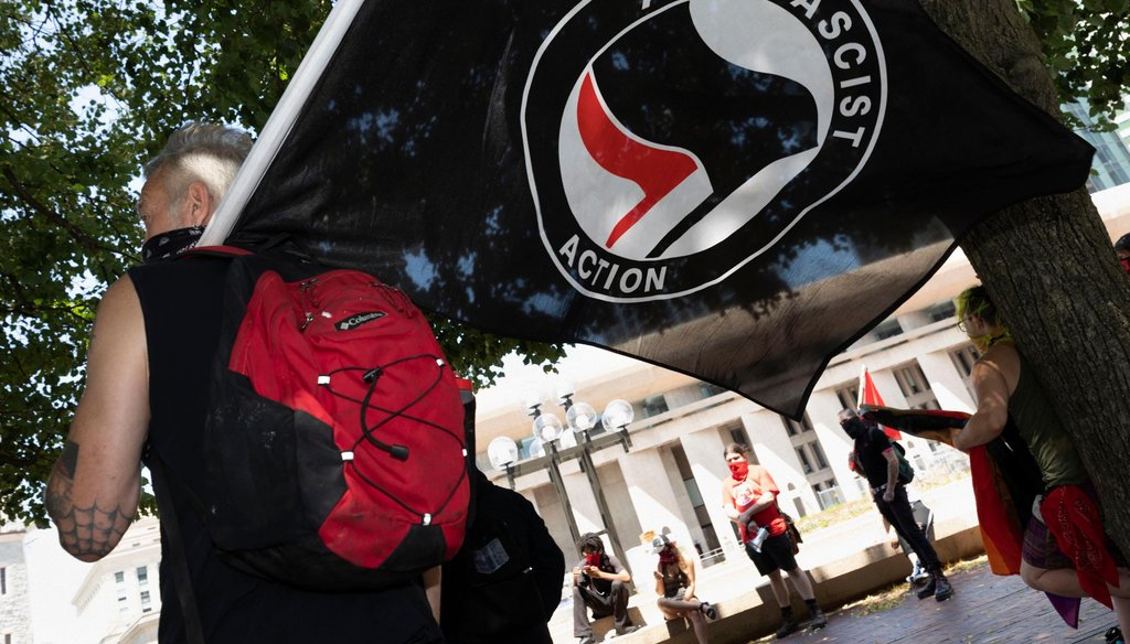 An anti-fascist protester holds a flag on the Christian Science Plaza on July 11, 2020, in Boston. (AP)