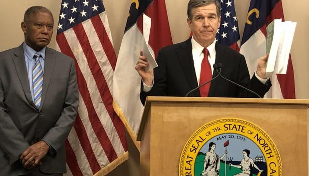 Gov. Roy Cooper holds the Republican budget in his left hand, his suggested changes in his right, as Senate Minority Leader Dan Blue looks on. (via WRAL)