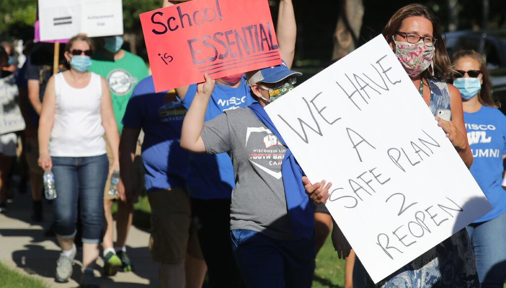 People hold signs during a march to the home of Milwaukee Mayor Tom Barrett, in Milwaukee on Sunday, July 19, 2020. (Mike De Sisti / Milwaukee Journal Sentinel)
