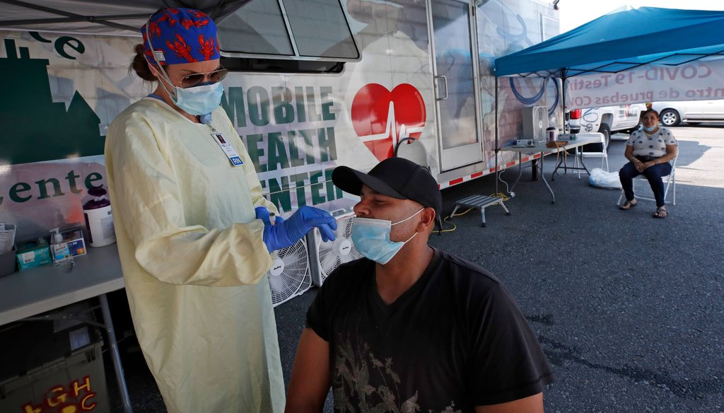 Nurse Tanya Markos administers a coronavirus test on patient Juan Ozoria at a mobile COVID-19 testing unit on July 2, 2020, in Lawrence, Mass. (AP)