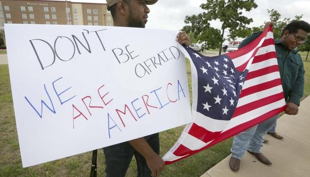 Joseph Offutt, left, and Raheem Peters hold a sign and U.S. flag near the site of the Garland, Texas, shooting of a cartoon contest event of the Muslim prophet Muhammad. (AP)