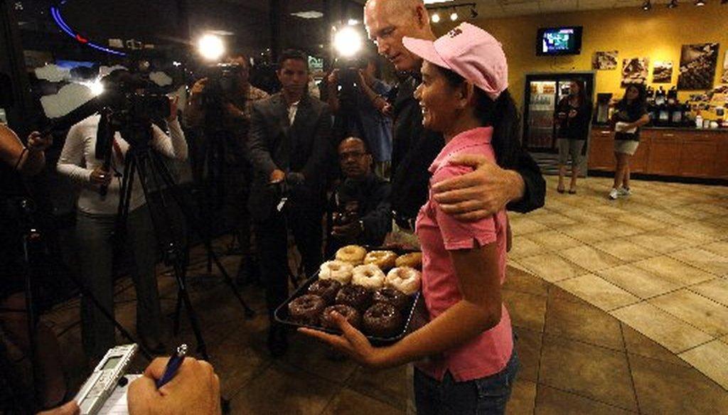 Rick Scott and Rachel Waatti talk doughnuts with members of the media at Nicola's Donuts.