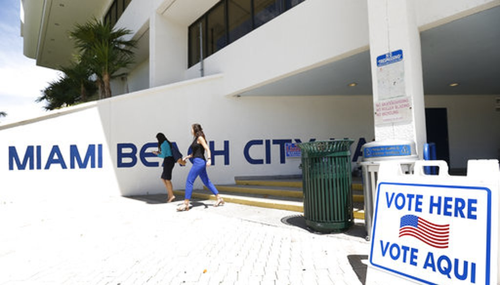 Pedestrians walk past a sign for a polling station at Miami Beach City Hall, Monday, Aug. 13, 2018, in Miami Beach, Fla. (AP)