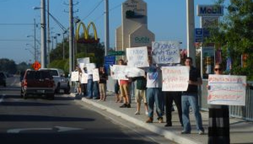 Demonstrators rally along a busy road in Tampa, Fla., to protest the Obama administration's energy policies.