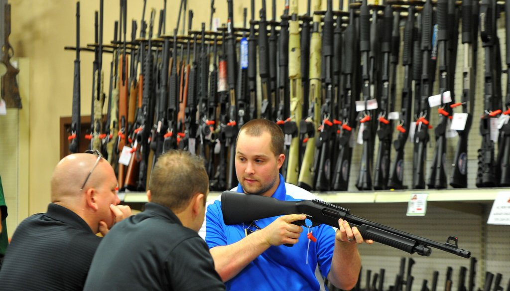 Adventure Outdoors salesman Adam James shows a shotgun to customers. The Smyrna, Ga. gun shop, shooting range and outdoor supply facility saw a 300 percent increase in gun sales shortly after the July 2012 movie theater shootings in Colorado.