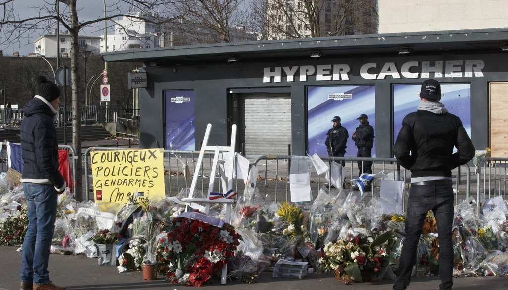 People look at flowers outside a kosher grocery store in Paris, where four people where killed in a terror attack Jan. 9. (AP Photo/Michel Euler)