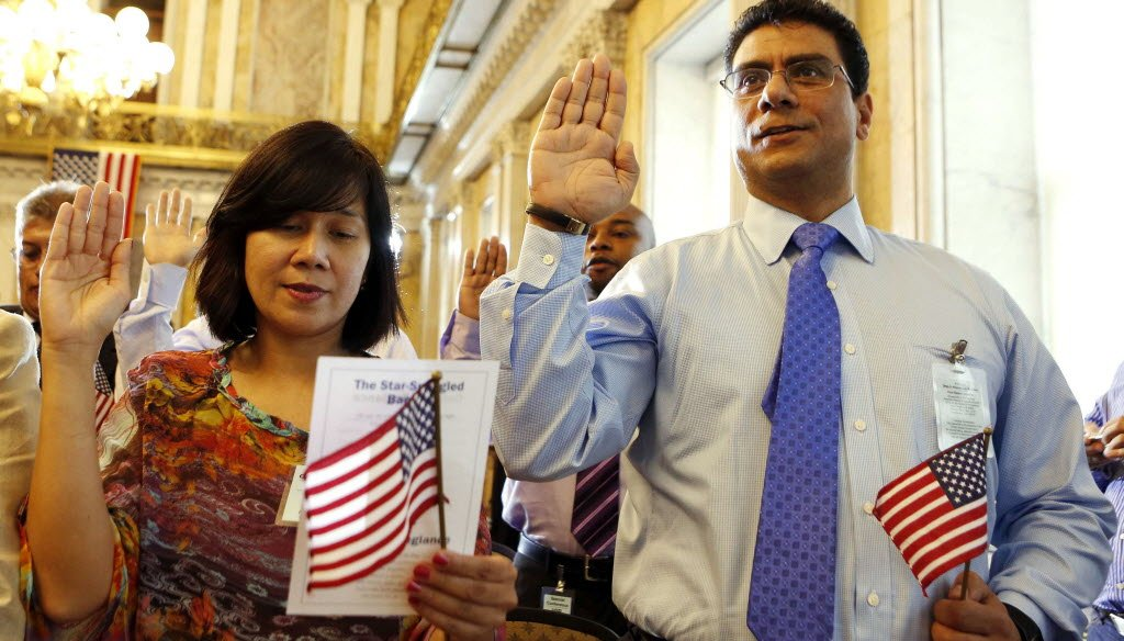 Candidates Noor Mononutu (on left) and Ashraf Mokhtar (on right) swear in as United States citizens during a Special Naturalization Ceremony for 30 U.S. citizen candidates at the U.S. Treasury Department in Washington, July 3, 2013. REUTERS/Larry Downing