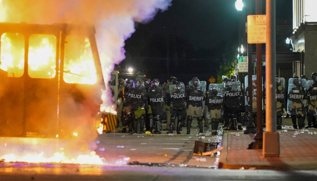Police stand near a garbage truck ablaze during protests over the shooting of Jacob Blake in Kenosha on Aug. 24, 2020.  (AP Photo/Morry Gash)