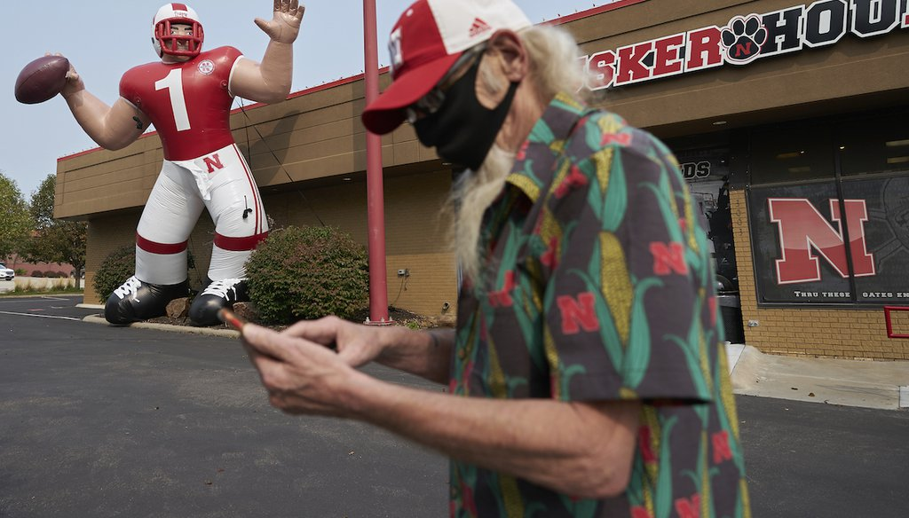 A fan stops to take a picture of a giant inflatable football player standing in front of the Husker Hounds sports apparel store in Omaha, Neb. Omaha has a mask mandate, but the state as a whole doesn't. (AP Photo/Nati Harnik)