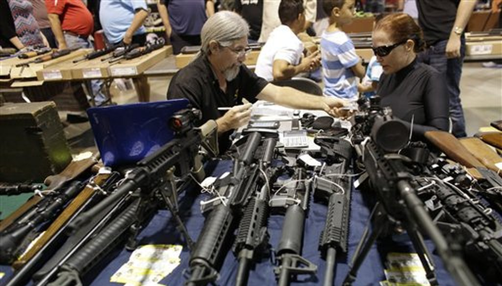 Harvey Kornnfield, owner of Airport Pawn, left, works on a sale with Bamula Schlesinger, right, at a gun show hosted by Florida Gun Shows, Saturday, Jan. 9, 2016, in Miami. Schlesinger purchased an Uzi and a Smith & Wesson 38. (AP)