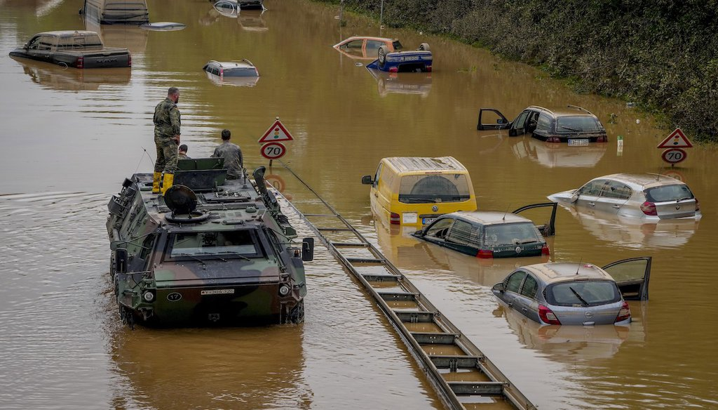 German army soldiers check for victims in flooded cars on a road in Erftstadt, Germany, after strong rainfall caused the Erft river to overflow, causing massive damage. (AP Photo/Michael Probst)
