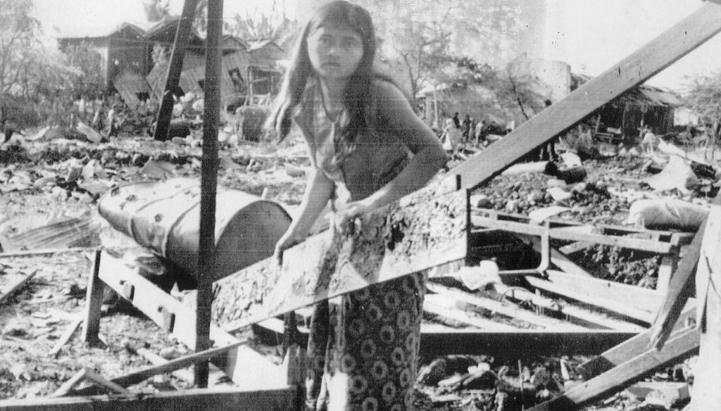 A Cambodian girl salvages a board from her home in Neak Luong, southeast of Phnom Penh, which was hit by a misdirected U.S. bombing raid. (Tampa Bay Times files)