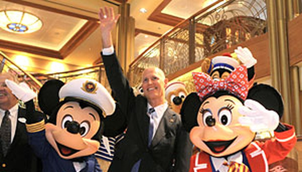 Rick Scott waves with Mickey and Minnie Mouse during a welcoming ceremony his first week in office aboard the new $900 million Disney Dream cruise ship in Port Canaveral.