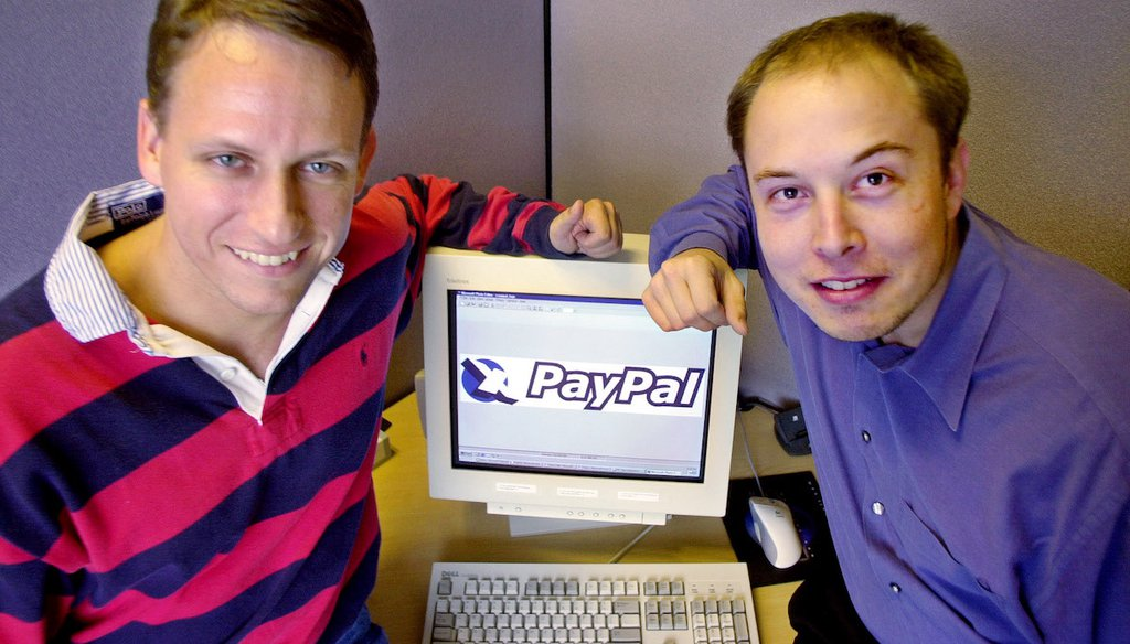 PayPal co-founders Peter Thiel, left, and Elon Musk pose with the PayPal logo at corporate headquarters in Palo Alto, Calif., Oct. 20, 2000. (AP)